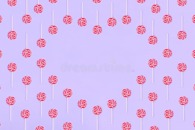 Hj?rta som g?ras ut ur lollypopgodisar p? rosa bakgrund, kopieringsutrymme S?tt barndombegrepp royaltyfri foto