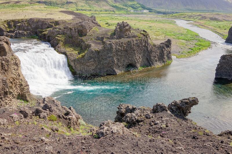 Hjalparfoss waterfall in Iceland with azure water viewed from the top of a hill stock photography