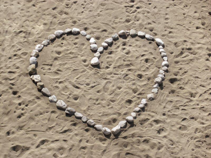 Hjortform som göras av ljusa stenar på sanden arkivfoton