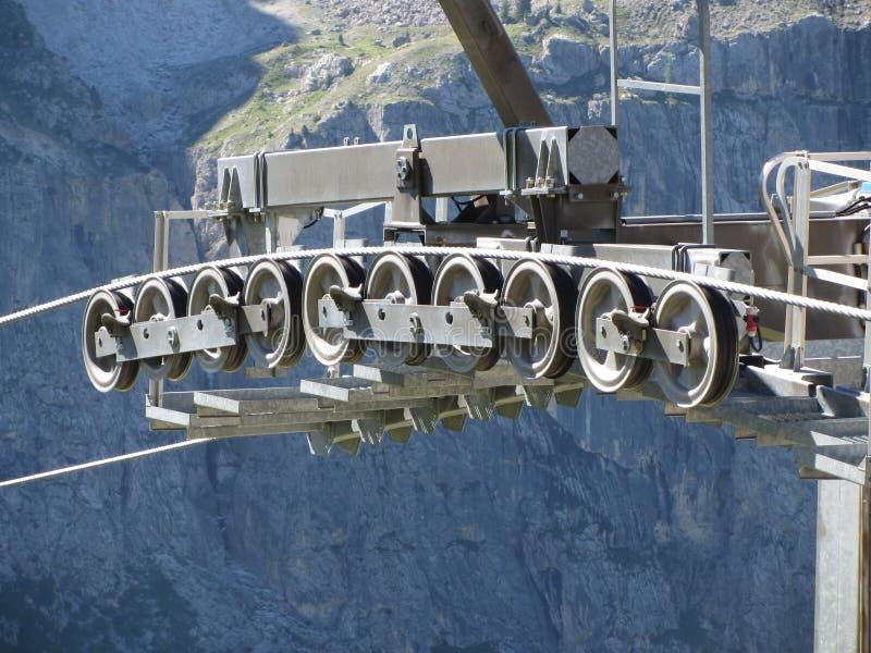 Hjul för kugghjul för kabelbil med bergbakgrund Rullar och block av skidliften arkivbild
