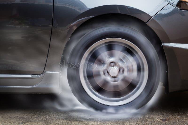 Hjulet för snurret för springa för bil bränner gummi på golv royaltyfria foton