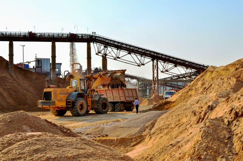 Hjulframdel-slut laddare som lastar av sand in i den tunga dumper Krossa fabriken, maskiner och utrustning f?r att krossa, maland royaltyfri fotografi