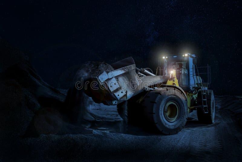 Hjulladdare som kammar hem grus på ett nattetidkonstruktionsprojekt arkivbilder