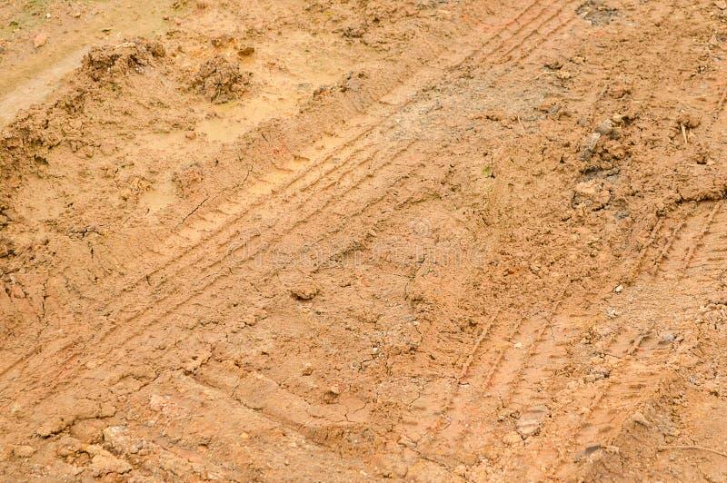 Hjulspår på smutsjordtextur, når att ha regnat arkivfoton