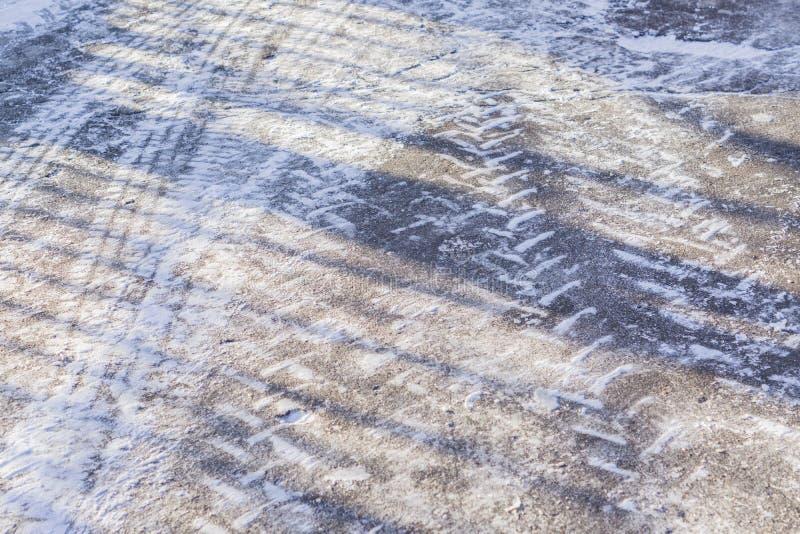 Hjulspår på vintervägen som täckas med insnöat en solig dag royaltyfri fotografi