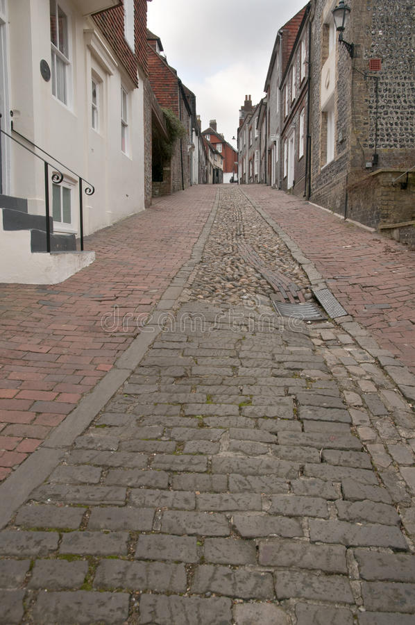 A hilly street in Lewes West Sussex. Cobbles and pavers lead up to old houses on a steep residential street in this quaint english town stock image