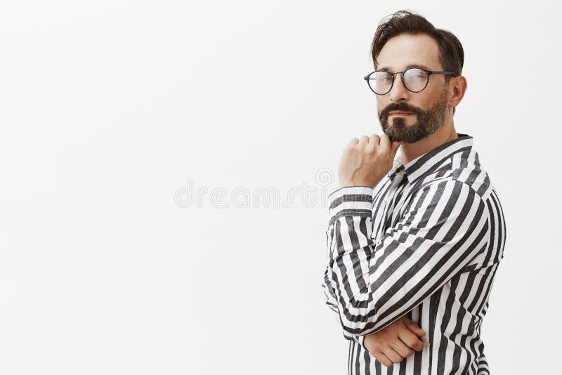 Hmm, συμπαθητική ιδέα, θα το χρησιμοποιήσω Στοχαστικός στρατηγικός στα γυαλιά και το ριγωτό πουκάμισο, που στέκονται στο σχεδιάγρ στοκ φωτογραφία