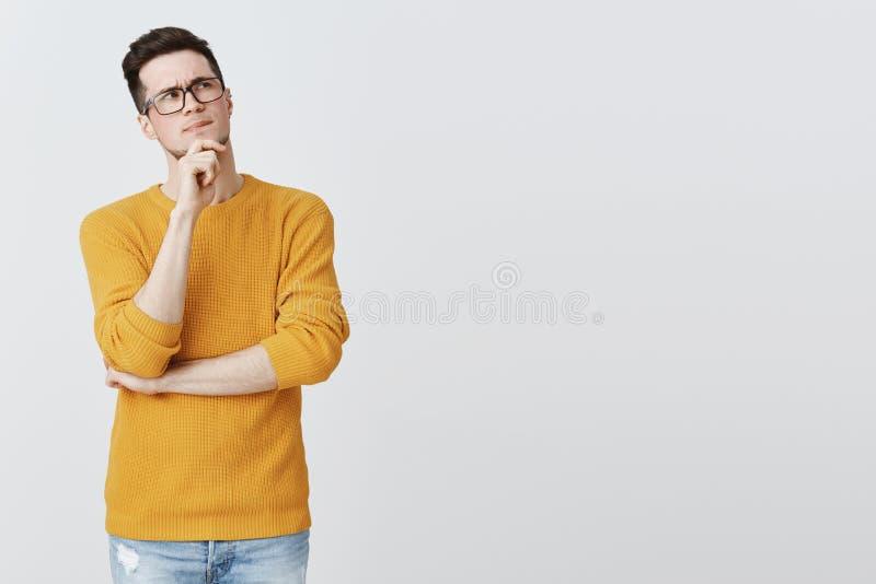 Hmm τι εάν Έξυπνος και στοχαστικός όμορφος τύπος στα γυαλιά geek και άνετο κίτρινο χέρι εκμετάλλευσης πουλόβερ στο πηγούνι στοκ φωτογραφίες