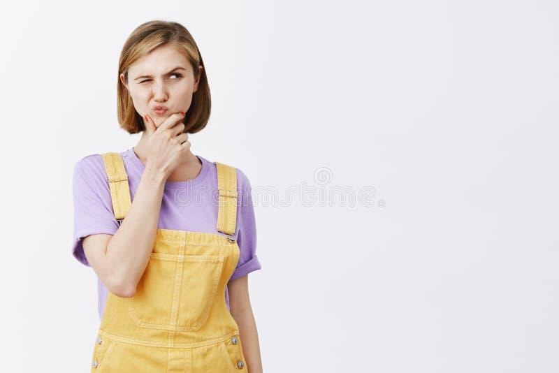 Hmm, τι εάν Πορτρέτο του ραδιουργημένου αμφισβητήσιμου έξυπνου αστικού θηλυκού στα μοντέρνα κίτρινα dungarees, ανυψωτικό φρύδι σε στοκ εικόνα