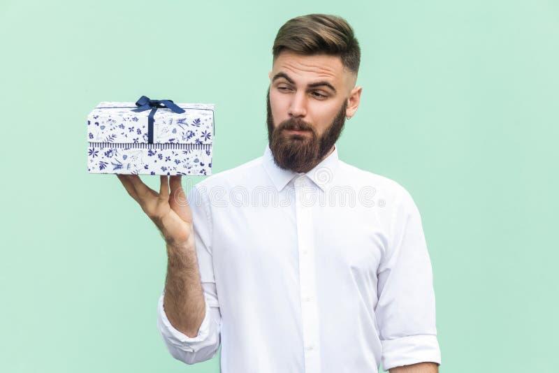 ¡Hmm cuál es él! El hombre barbudo que mira la caja de regalo y quiere demasiado abierto fotos de archivo