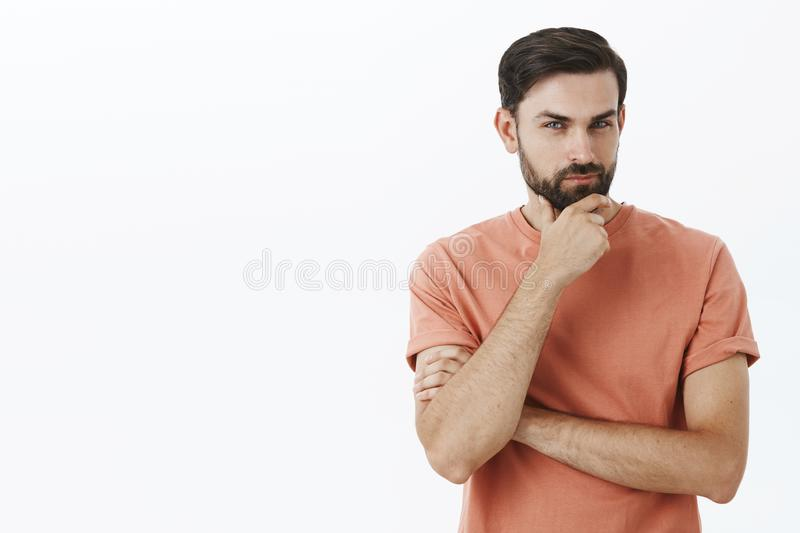 Hmm I am listening. Intrigued and interested handsome male 30s entrepreneur rubbing beard and squinting delighted. Smirking as thinking, listening to good idea stock images