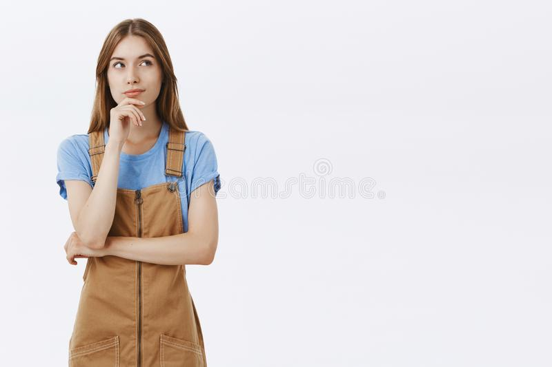 Hmm I wonder what cook today. Portrait of creative good-looking thoughtful young caucasian female in brown overalls royalty free stock photos