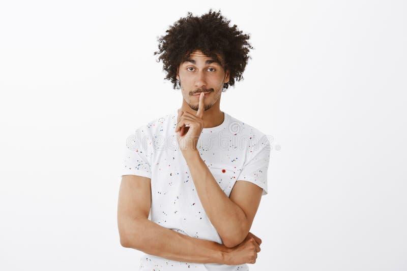 Hmm, ideia agradável Retrato do indivíduo despreocupado bonito intrigado com pele escura e cabelo encaracolado, guardando o dedo  fotografia de stock