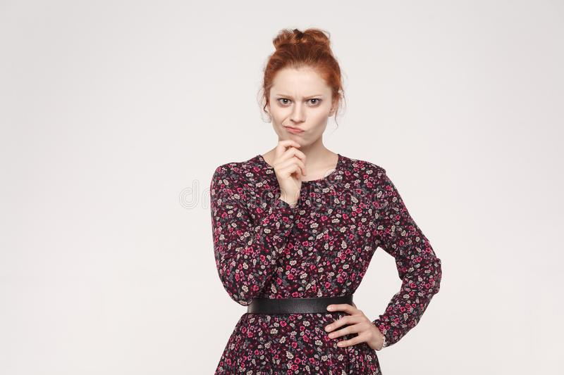 Hmm. Isolaited studio shot on gray background of cute redhead woman with looking at camera and planning something. stock photography