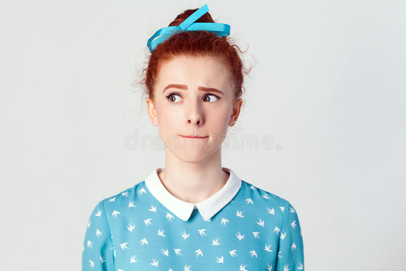 Hmm. Let me think. isolated studio shot on gray background of cute redhead girl with looking sideways and planning something.  stock image