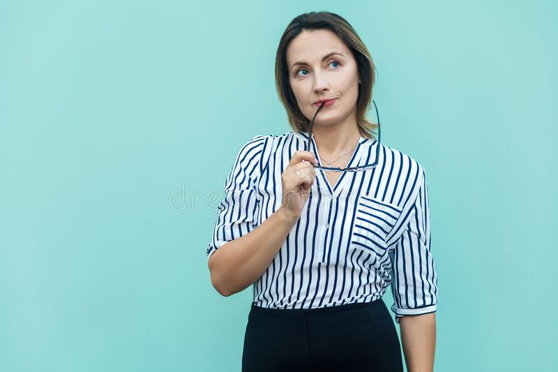 Hmm. Let my think. Blonde business woman boss wondering and imagination, and holding glasses. royalty free stock image