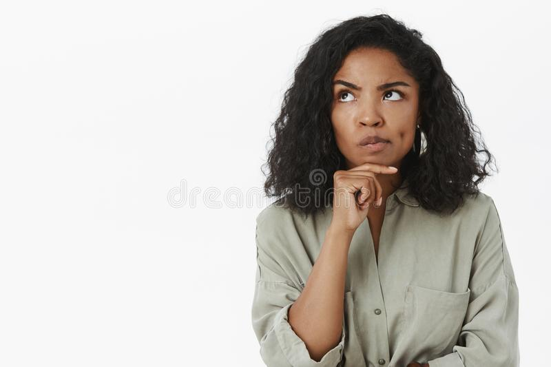 Hmm, maybe it work. Portrait of serious-looking thoughtful and smart businesswoman smirking and frowning looking up with stock photos