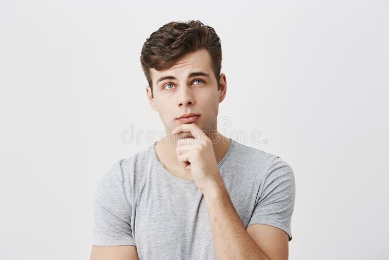 Hmm no malo El estudiante masculino pensativo concentrado que evalúa sus ocasiones de aprobar el examen, guarda la mano en la bar foto de archivo