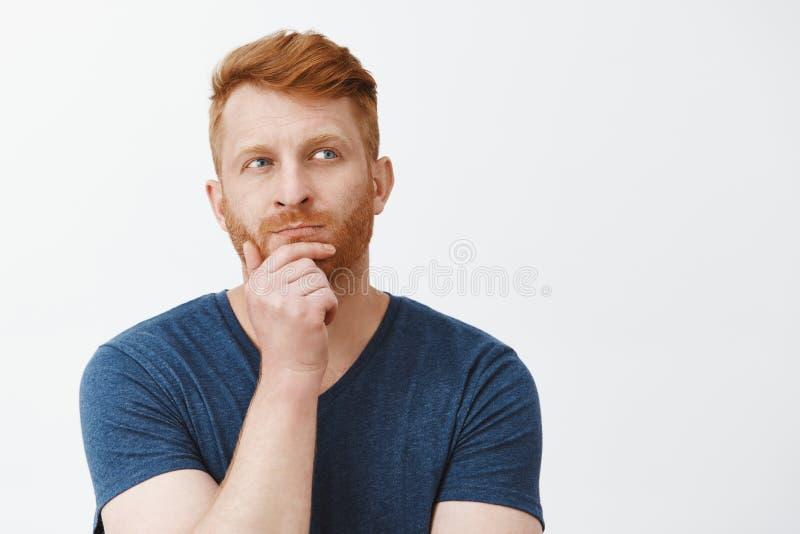 Hmm pozwala my myśleć Portret skupiający się kreatywnie i mądrze atrakcyjny męski strateg z czerwonym włosy, stoi wewnątrz zdjęcie royalty free