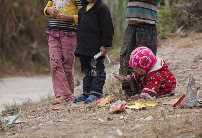 Hmong barn som äter godisen på den smutsiga jordningen i Dong Van den steniga platån royaltyfria bilder