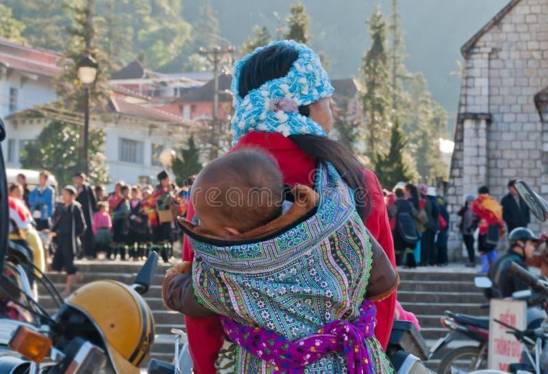Hmong-Frau, die ihr Kind in ihrem Rucksack trägt. Sapa. Vietnam lizenzfreie stockfotos