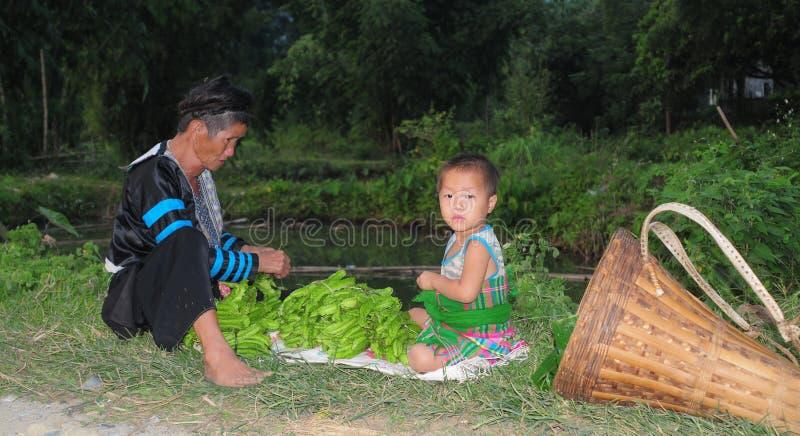 Hmong-Frau mit ihrem Sohn, der auf Straße in Hagiang, Vietnam sitzt lizenzfreie stockbilder