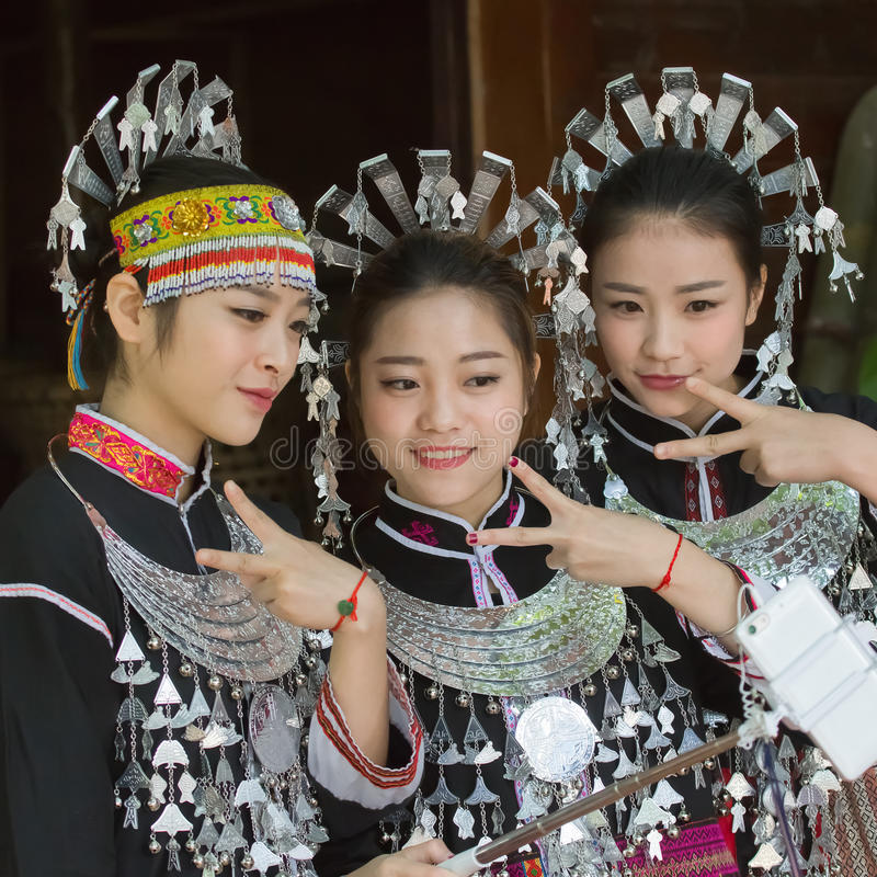 Hmong girls on their traditional dresses. These girls are Hmong nationality in China. They weave their traditional cloth and make their traditional garments stock photos