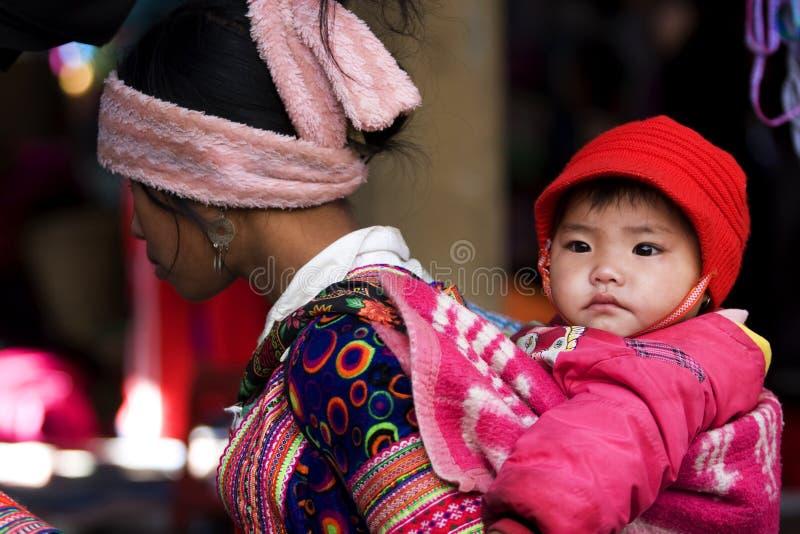 Hmong kvinna med hennes barn på baksida arkivfoto