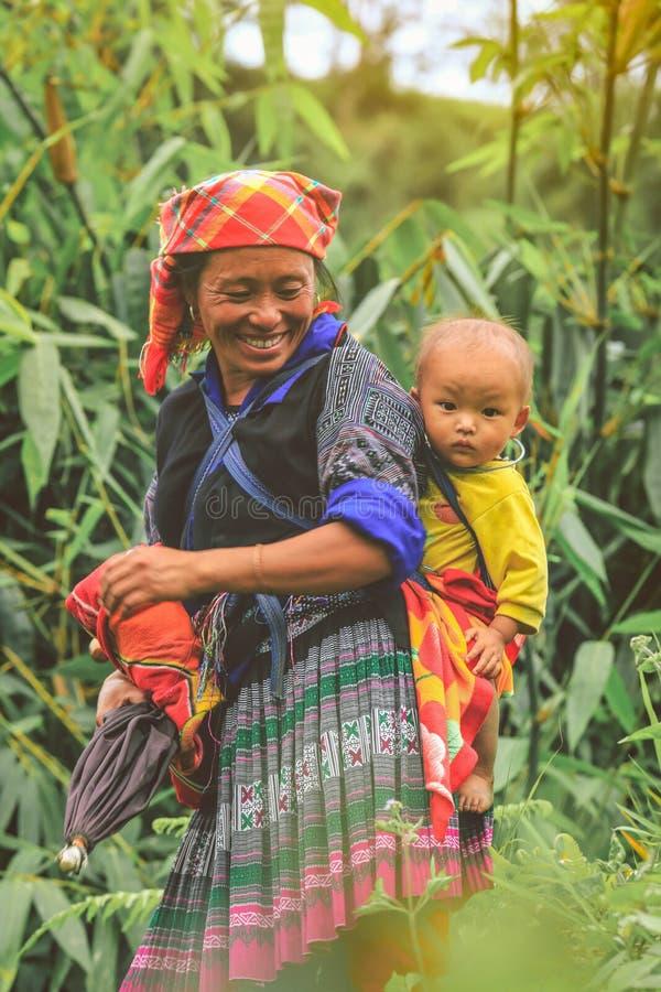 Hmong stam Oman som bär hennes barn i hennes ryggsäck i Vietnam royaltyfri fotografi