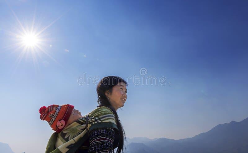 Hmong stamkvinna som tillbaka bär hennes barn på henne i Sapa, Vietnam arkivfoton