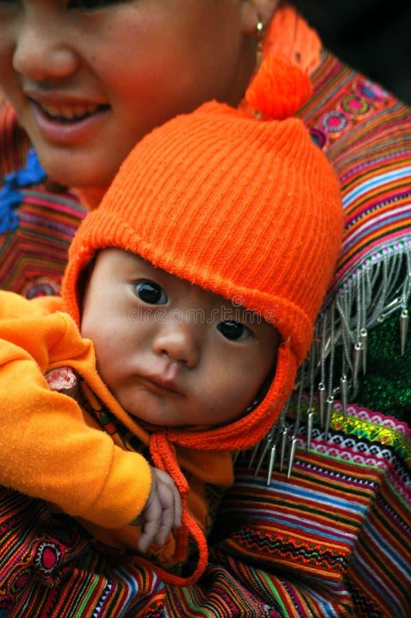 Hmong-Stammfrau, die ihr Kind, Bac Ha, Vietnam trägt lizenzfreie stockfotos
