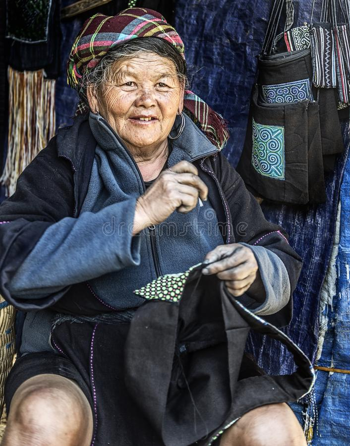 Hmong tribal old woman hand tailoring bags in her shop, Sapa, Vietnam. SAPA VIETNAM MARCH 2015: Hmong tribal old woman hand tailoring bags in her shop, Sapa stock image