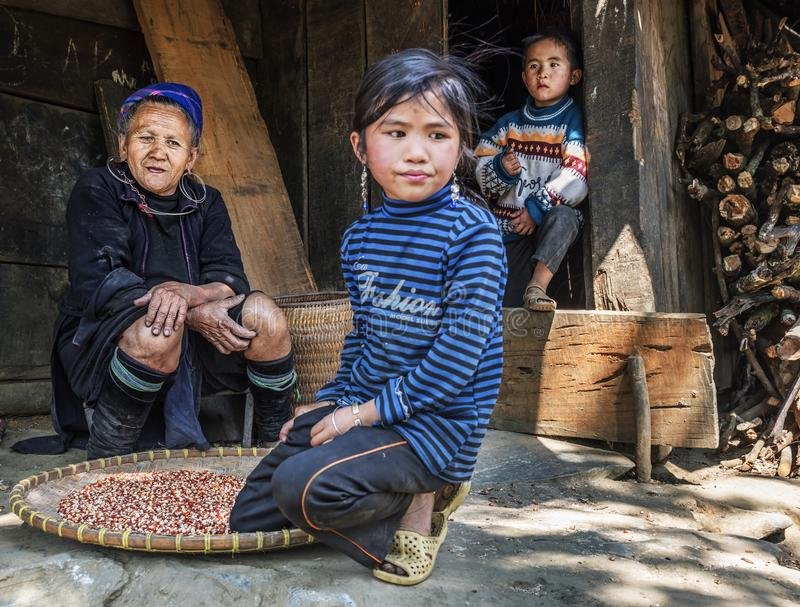 Hmong tribe grandmother resting outside her house with her two grandchildren in a small village, Sapa, Vietnam. SAPA VIETNAM MARCH 2015: Hmong tribe grandmother stock images