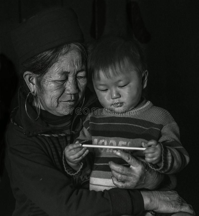Hmong tribe old lady holding her grandson in her arms inside her house, Sapa Vietnam royalty free stock images