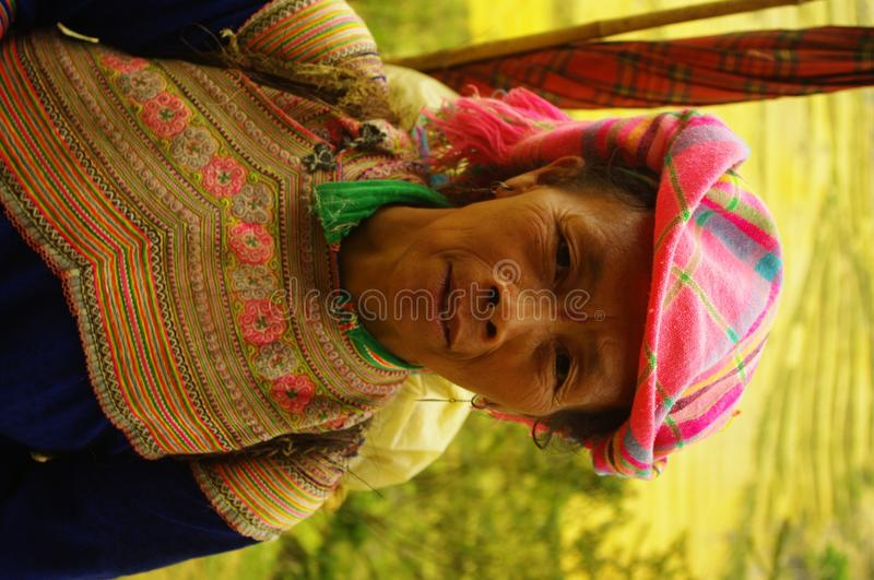 Hmong Women flowered. Hmong woman back from the flower market of Muong Khuong. Basket loaded, the eternal umbrella for sun protection such as thunderstorms stock photography