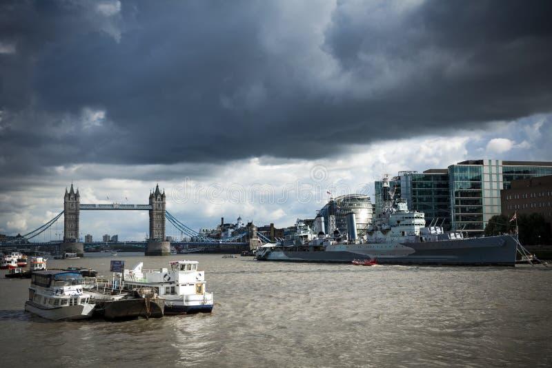 HMS Белфаст и мост башни под унылыми небесами стоковое изображение