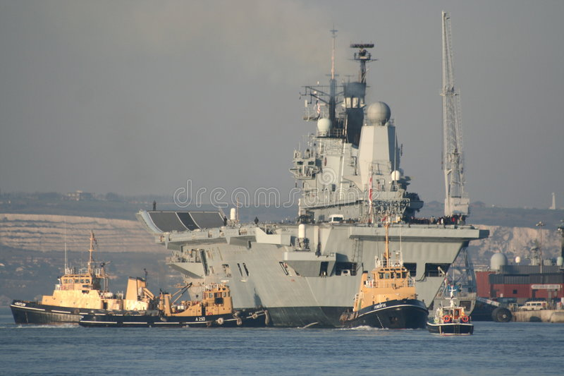HMS Ark Royal returns home. HMS Ark Royal, escorted by three tugs and the military police, returns to her home port, Portsmouth, UK, after exercises in the stock photography