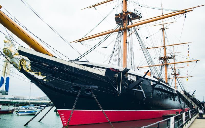 Hms-krigare som anslutas i Portsmouth England arkivbild