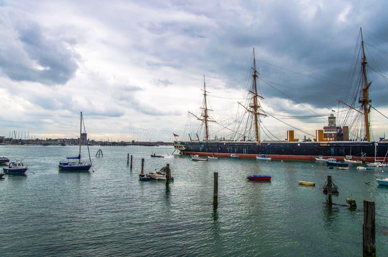 Hms-krigare som omges av fartyg på Portsmouth arkivbild