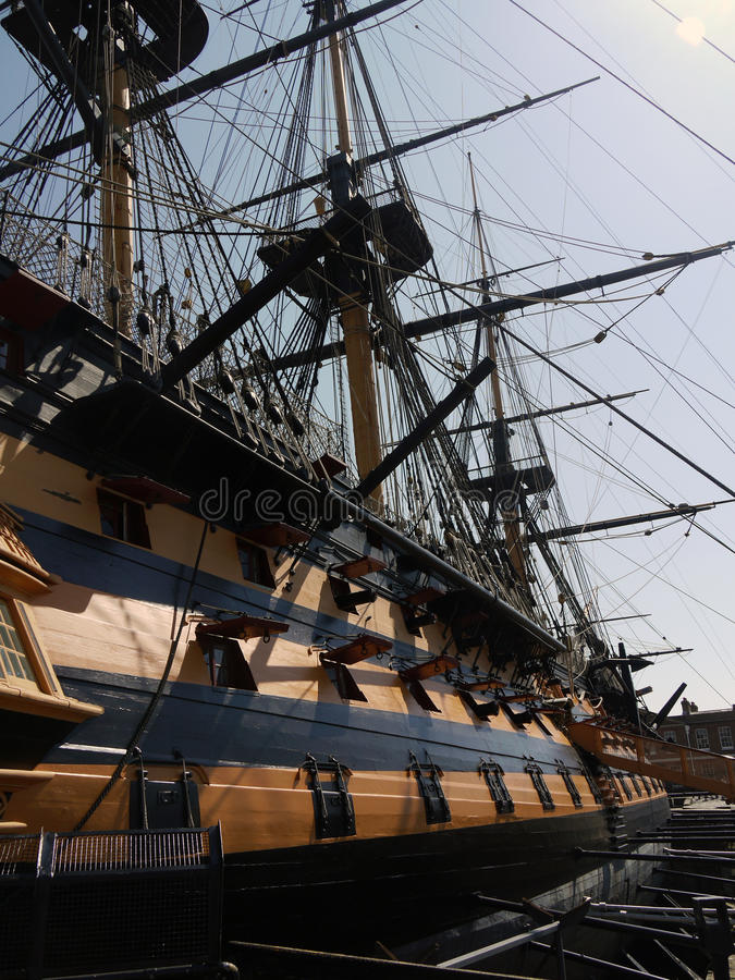 HMS Victory at Portsmouth harbour dock. HMS Victory man of war at Portsmouth harbour dock showing gun ports and length of ship in early morning sunshine royalty free stock photo