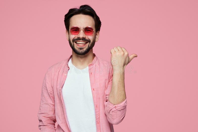 Hndsome har den unga skäggiga pojken i stilfull skjorta på kopieringsutrymme på den rosa väggen så visar något som är angenäm, at royaltyfri foto