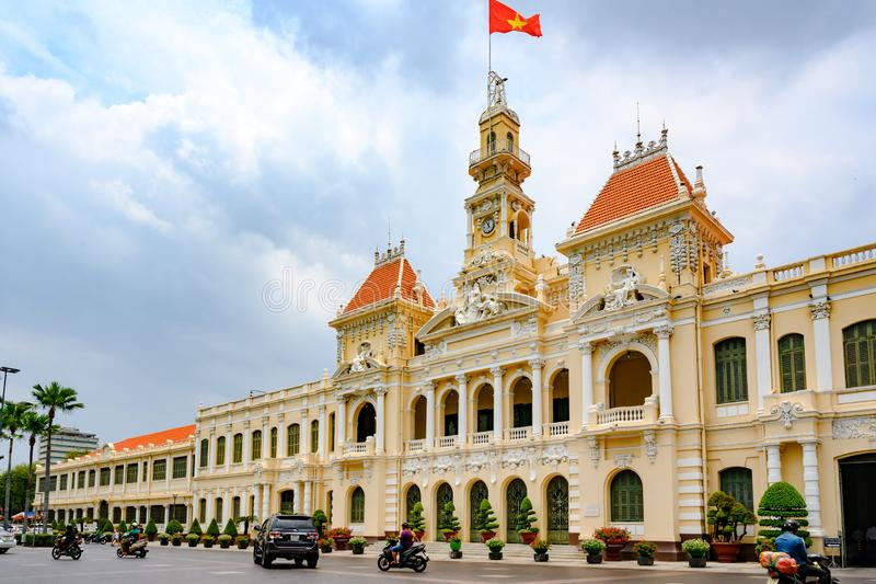 Ho Chi Minh City Hall with Vietnamese flag on top of roof tower. City Hall of former Saigon royalty free stock photography