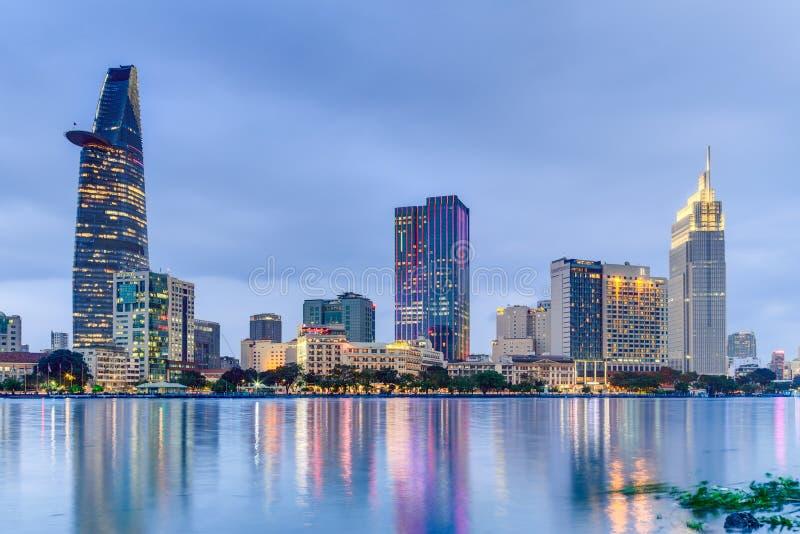 HO CHI MINH CITY, SAIGON/VIETNAM - CERCA DO AGOSTO DE 2015: As luzes da skyline do centro de Saigon são refletidas no rio imagem de stock