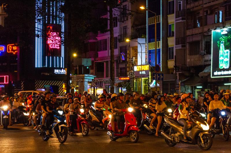 Night motorbike traffic Saigon Ho Chi Minh City Vietnam. Ho Chi Minh City, Vietnam - May 13, 2018: Motorbikes traffic at a intersection in central Saigon by stock photos