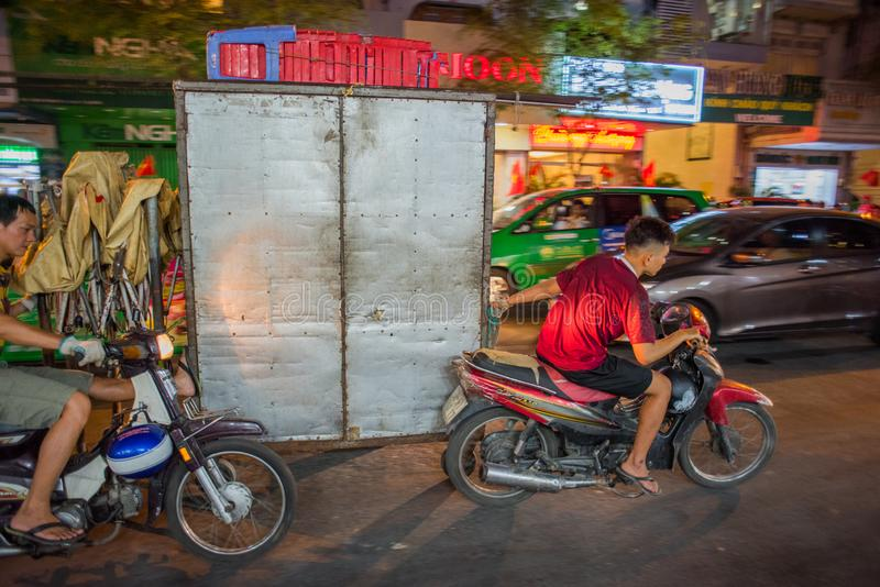 Ho Chi Minh City, Vietnam: two men on scooters pull a bulky wheeled metal construction royalty free stock photos