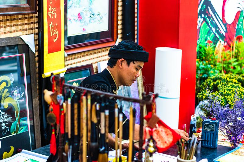 Ho Chi Minh City, Vietnam – 2019. Vietnamese man in ao dai, write Chinese writing or calligraphy at spring fair in Ho Chi Minh, royalty free stock photography