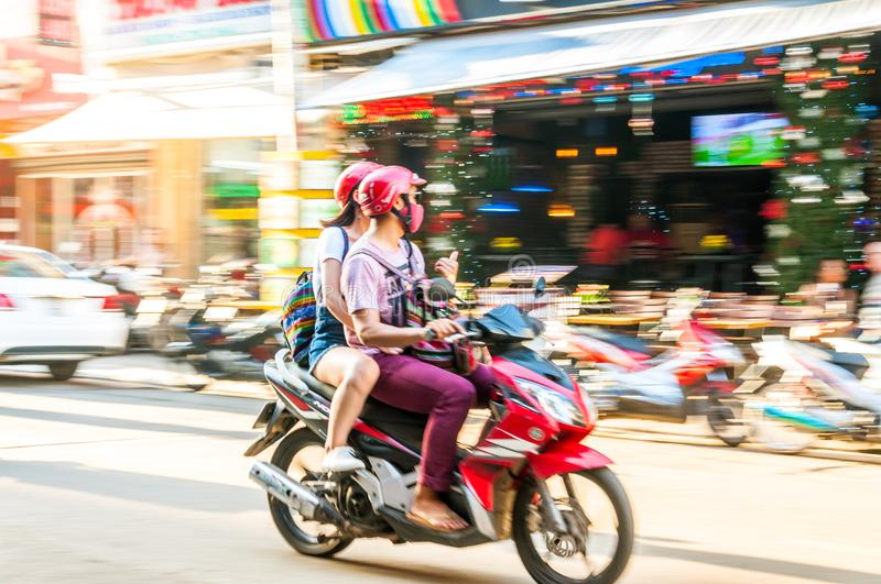 Ho Chi Minh City, Vietnam, 12,26,2017 Young couple guy and girl. Ride a moped around the city on a sunny day. Photo in motion with grease and no clear focus stock photo
