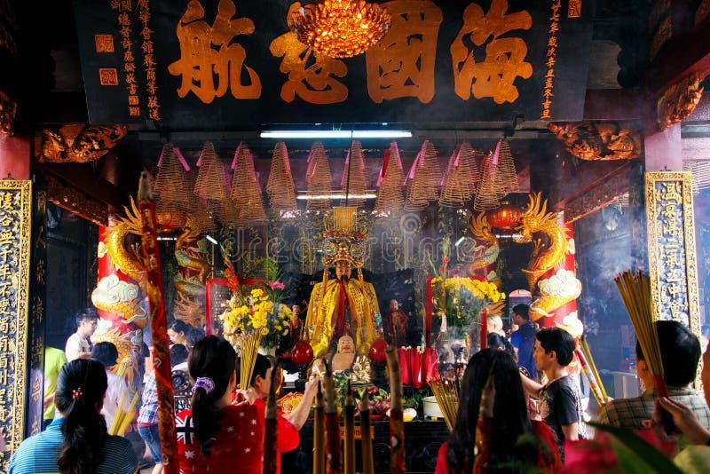 HO CHI MINH CITY, VIETNAME - 5 DE JANEIRO 2015: Vista nos crentes budistas dentro do templo chinês que rezam no altar colorido imagem de stock royalty free