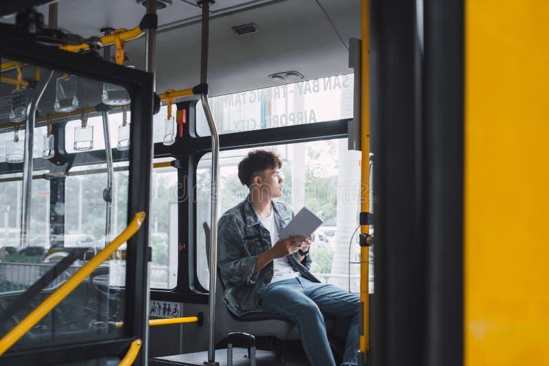 HO-CHI-MINH-STAD, VIETNAM - 22 JULI, 2017: Vervoer Mensen in de bus Hij lezingsboek in vervoer royalty-vrije stock afbeelding