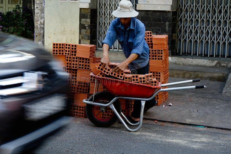 "Ho Chi Minh, Vietnam †""18 December, 2017: de oude mens schikt de baksteen op de kar stock foto"